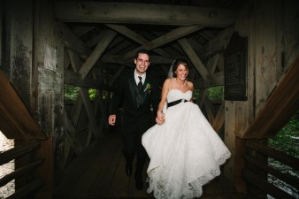 Bride and groom running on bridge
