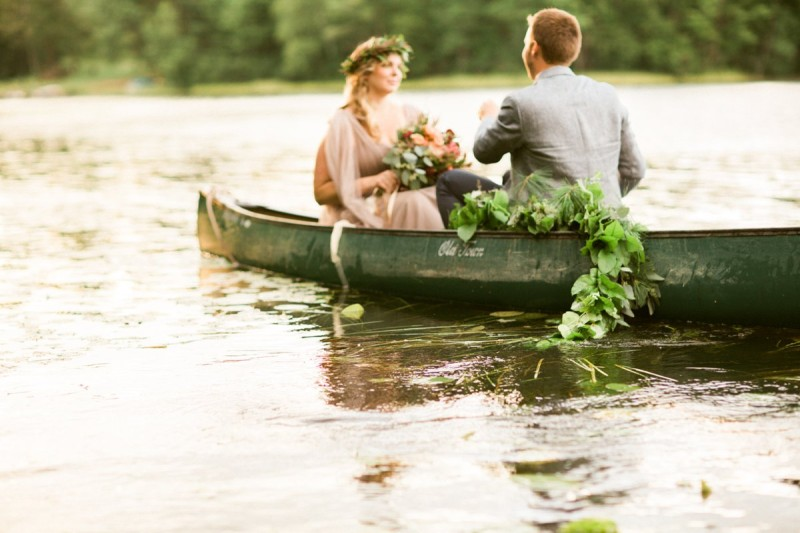 Bride and groom in canoe on lake in northern wisconsin